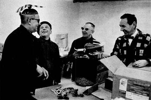 "The propeller beanie drew laughs from Belgian workmen as they unpacked display shipments to show ""How America Lives"" for the U.S. exhibit at the Brussels Fair, as shown in Life magazine in 1958."