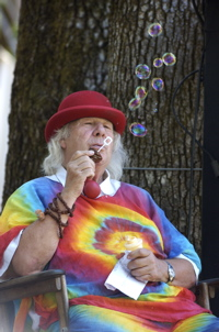 Wavy Gravy, inventor of the propeller cap, blowing soap bubbles.